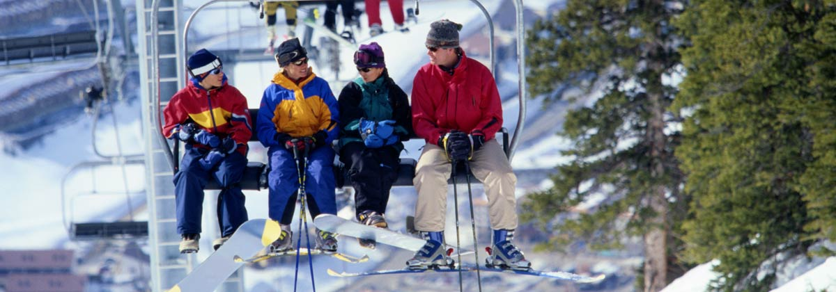 Skiers and snowboarders on a ski lift in Aspen, Colorado