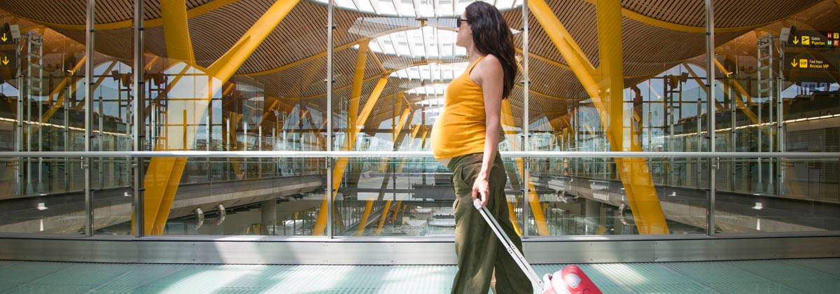 Woman in airport traveling while pregnant