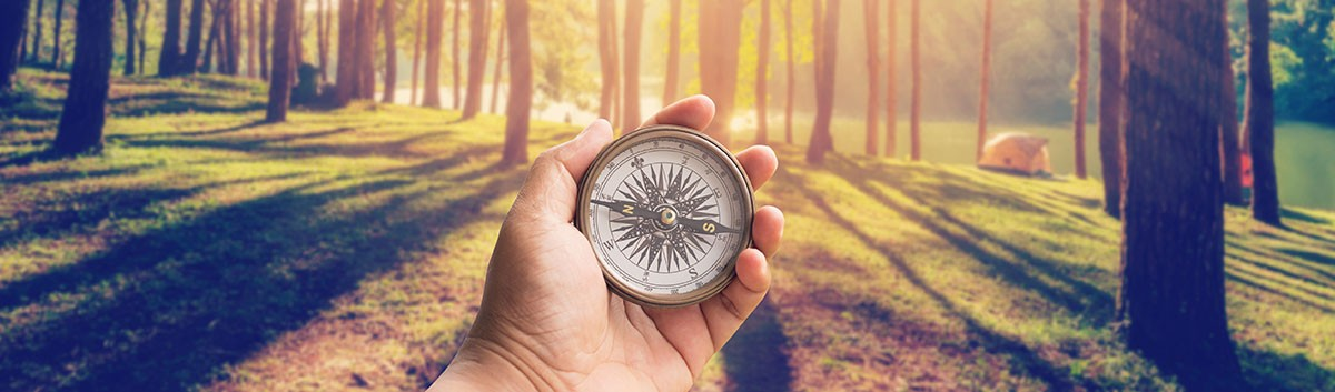 person with compass in forest