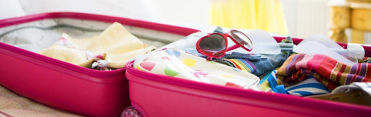 woman packing for a cruise with open suitcase