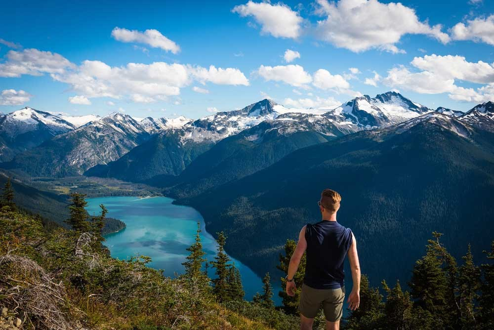 man looking at view of mountains, lake and forest in Whistler, Canada