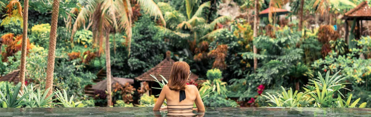 woman in infinity pool looking at jungle in Bali