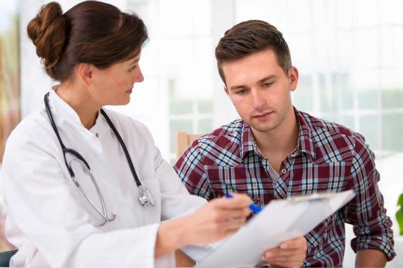 man talking with doctor holding papers
