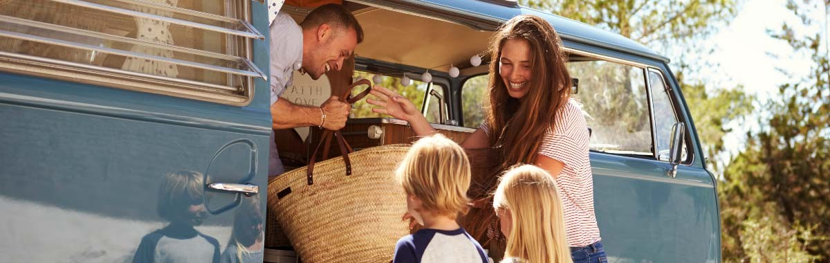 Family in blue camper van on a road trip vacation
