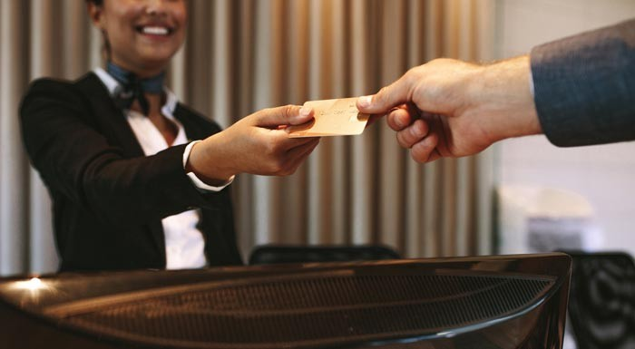 man handing credit card to hotel concierge